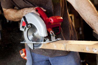 A carpenter cuts through wood with a circular saw.