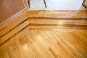 Red birch flooring and walnut band by Blade Millworks